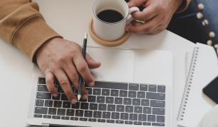 Man typing on a laptop keyboard